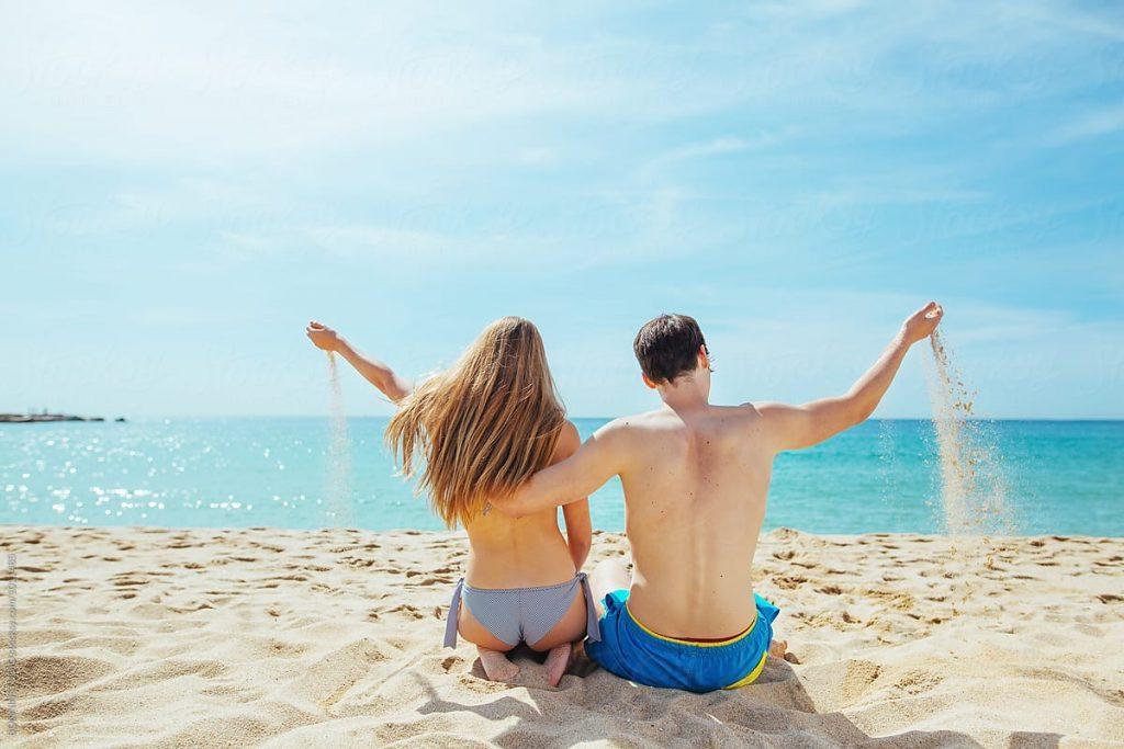 pareja de espaldas sentados en la arena de una playa